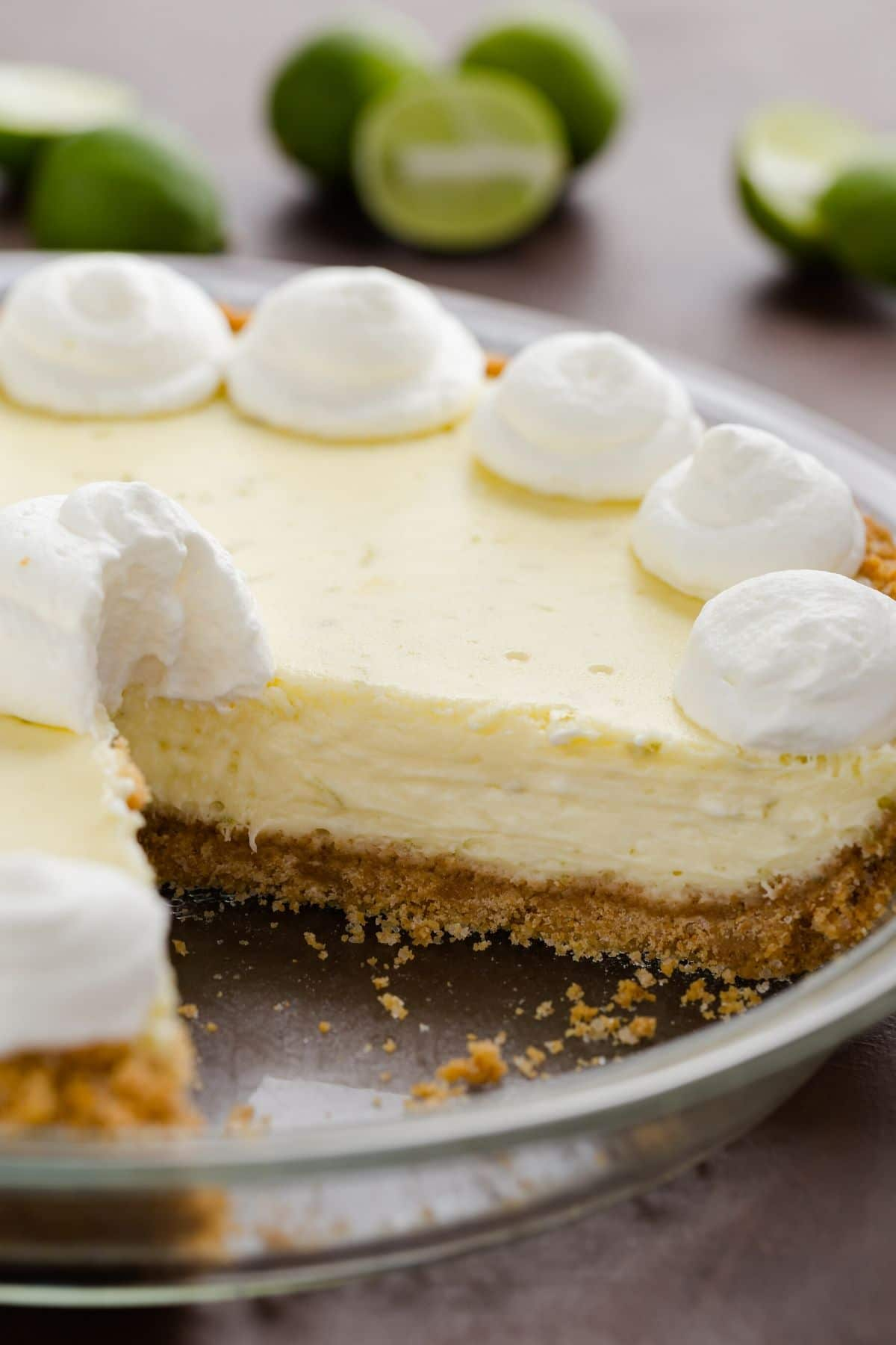 Side view of key lime cheesecake pie with a slice taken out.