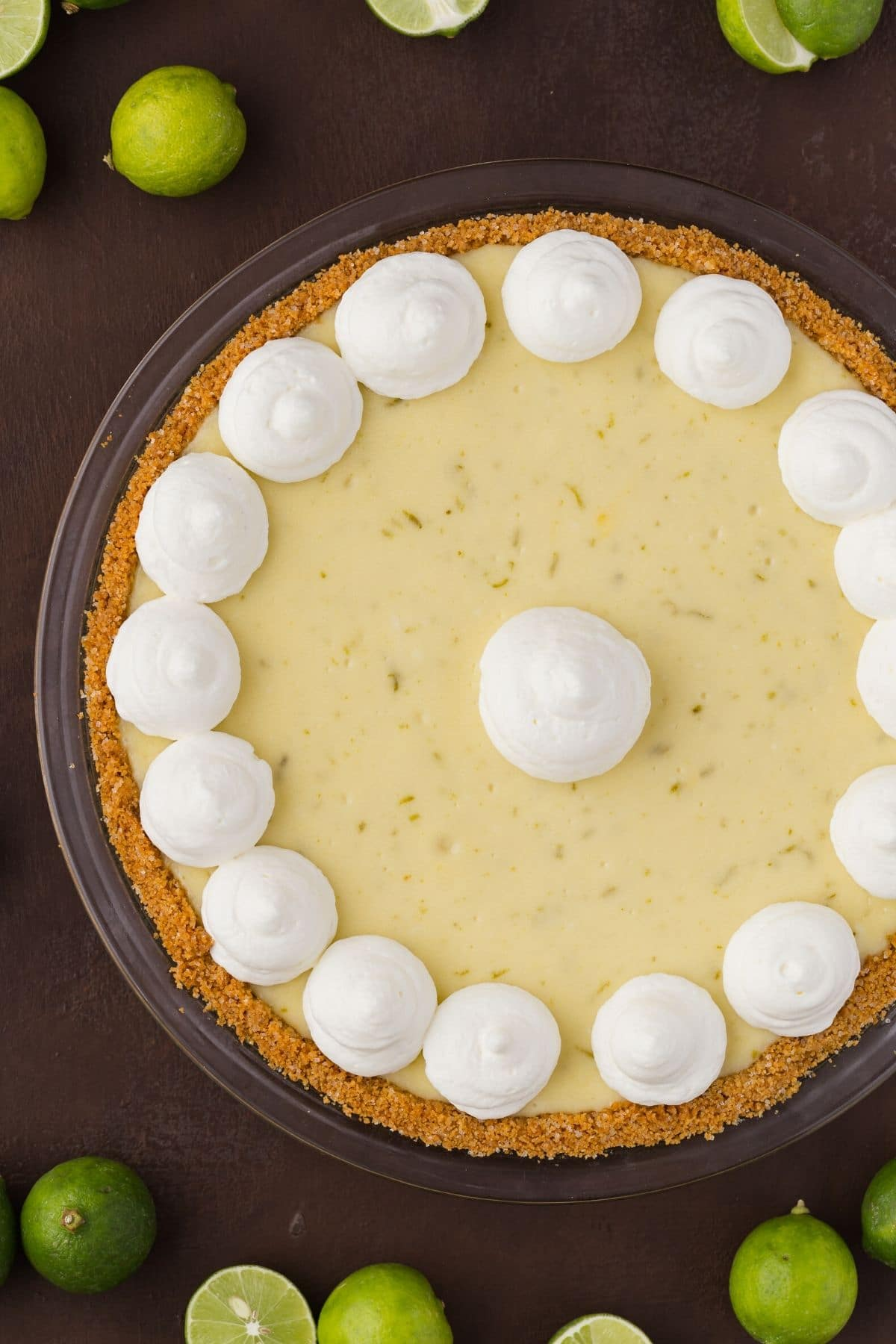 Close overhead view of a whole key lime cheesecake pie with swirls of whipped cream on top.