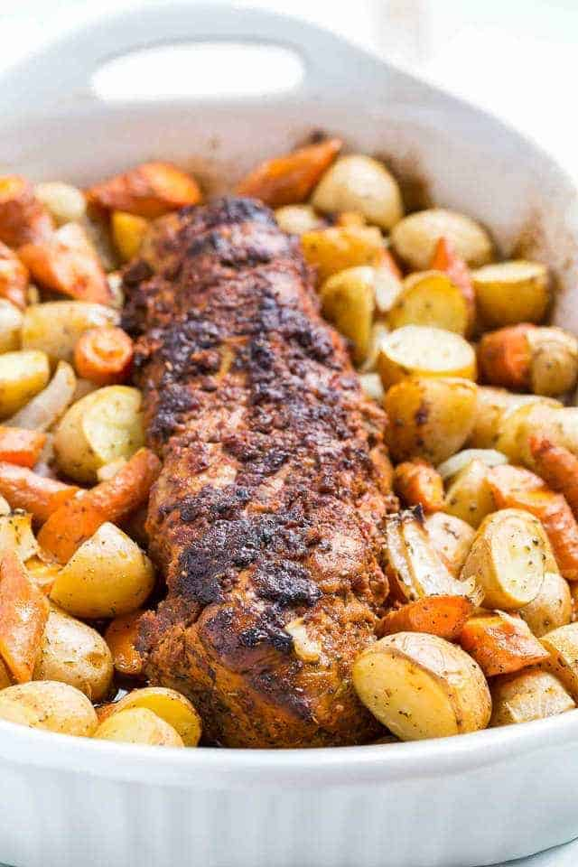 Angled view of Tomato Roasted Pork Loin with potatoes and carrots in a white casserole dish.