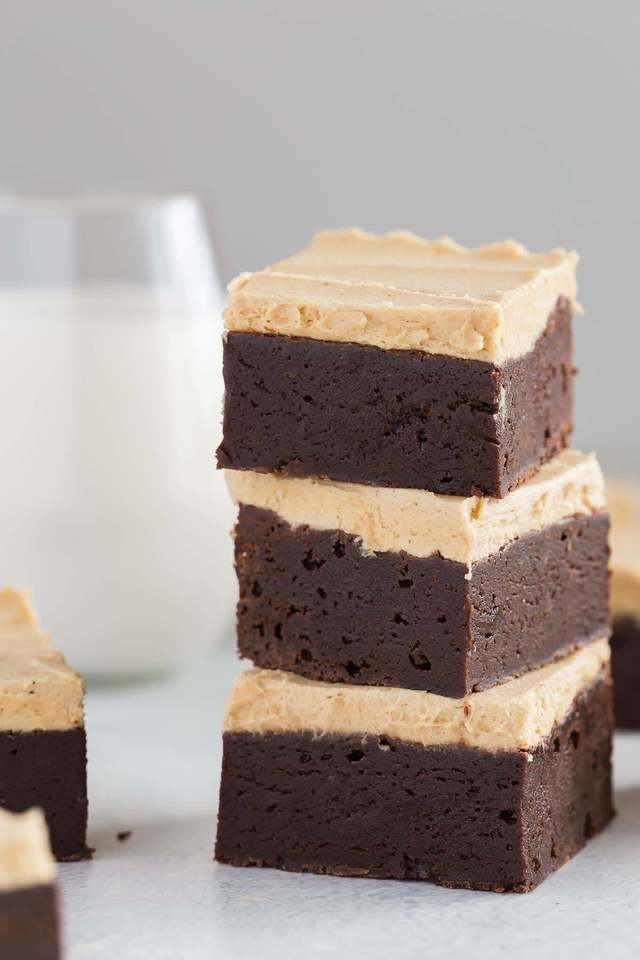 a stack of three fudgy brownies with peanut butter frosting