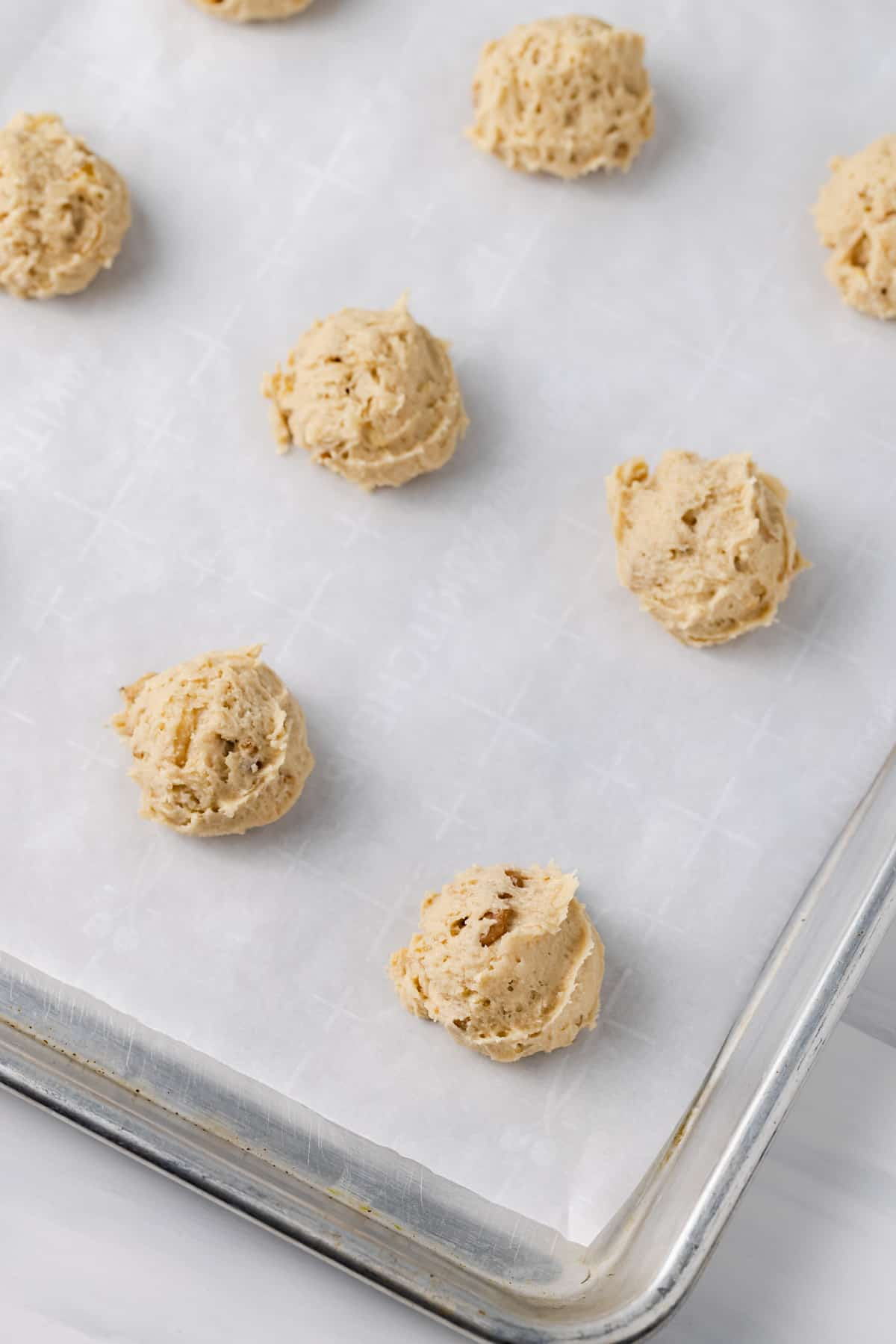 Scoops of banana bread cookie dough on a baking sheet