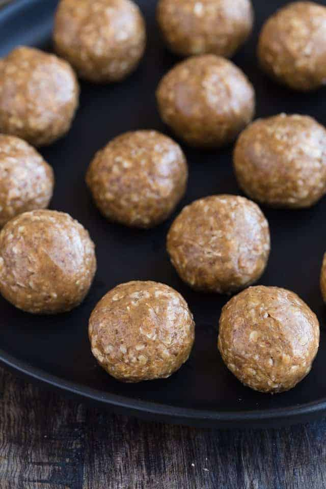 Close up view of almond butter oat balls on a black plate.