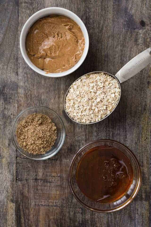 Almond butter, oats, flaxseed meal, and honey arranged in bowls on a wooden surface.