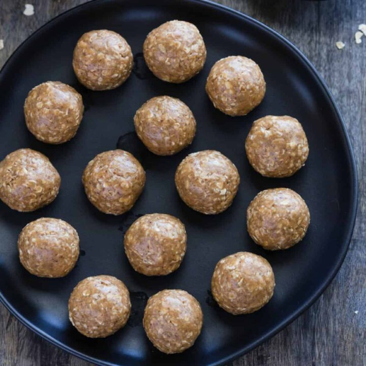 No Bake Almond Butter Balls neatly arranged on a black plate