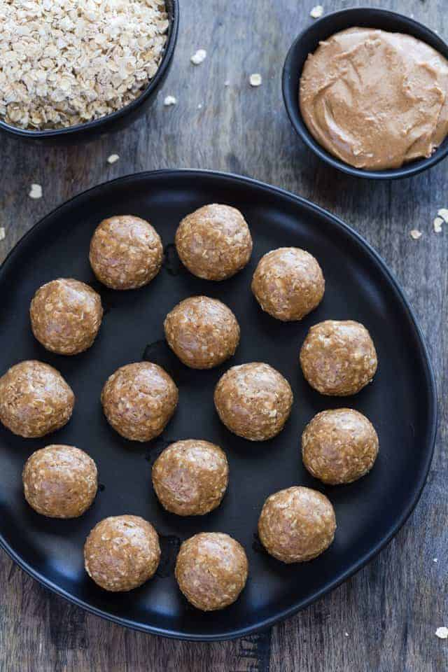 No Bake Almond Butter Balls neatly arranged on a black plate with a bowl of honey and a bowl of oats sitting behind the plate.