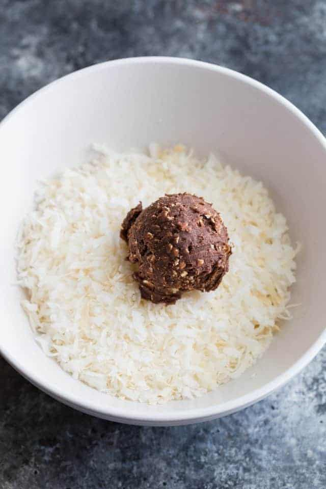 A chocolate peanut butter ball being rolled in shredded coconut.