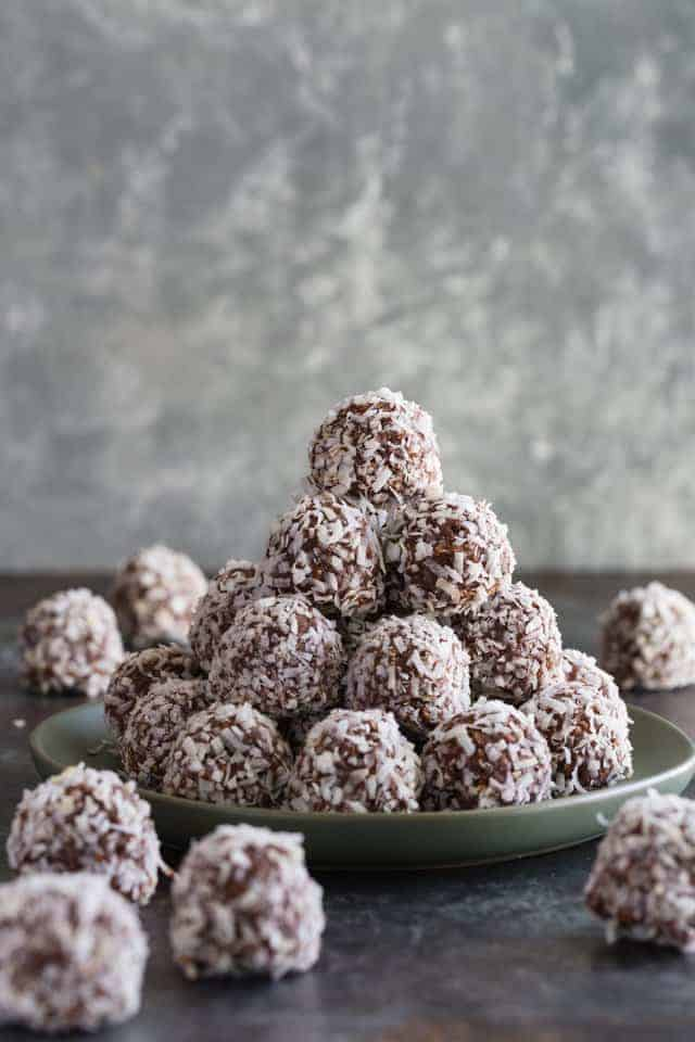 Chocolate peanut butter balls rolled in coconut stacked neatly on a green plate.