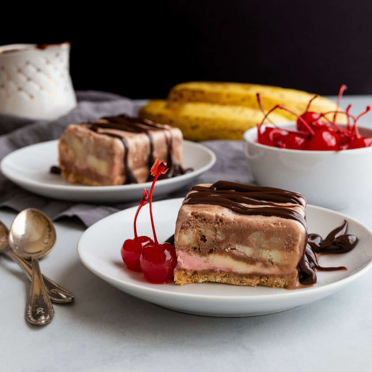 side view of a slice of no-bake banana split cake on a white plate with cherries