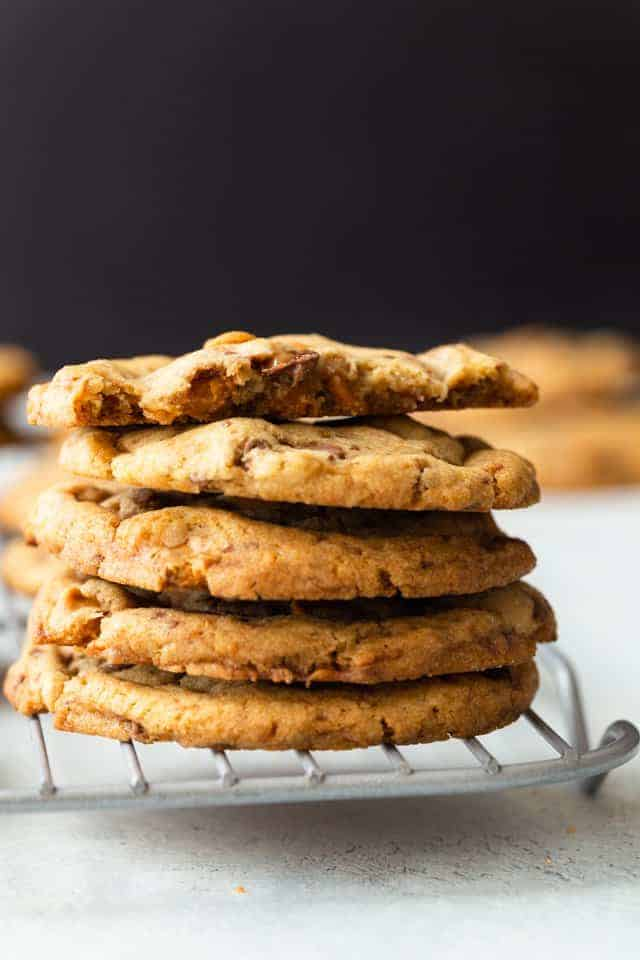 four and a half butterscotch toffee cookies stacked on a wire rack