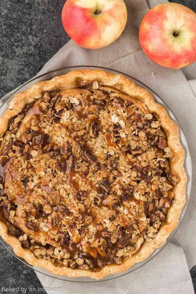Overhead view of a caramel apple pecan streusel pie in a glass dish.