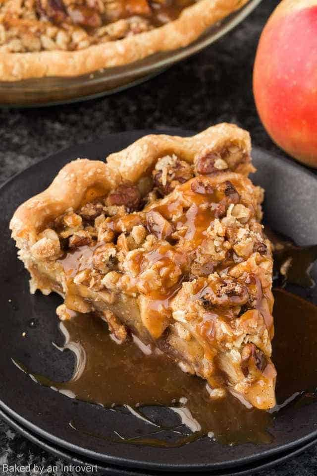 A slice of caramel apple pecan streusel pie on a black plate.