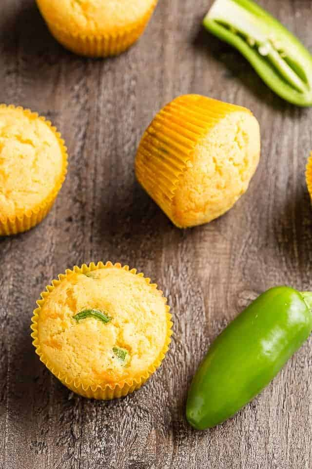 Cheddar Jalapeno Cornbread Muffins and whole jalapenos on a wooden table.
