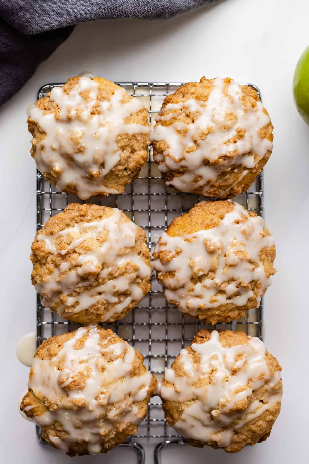 Apple streusel muffins topped with glaze on a wire rack