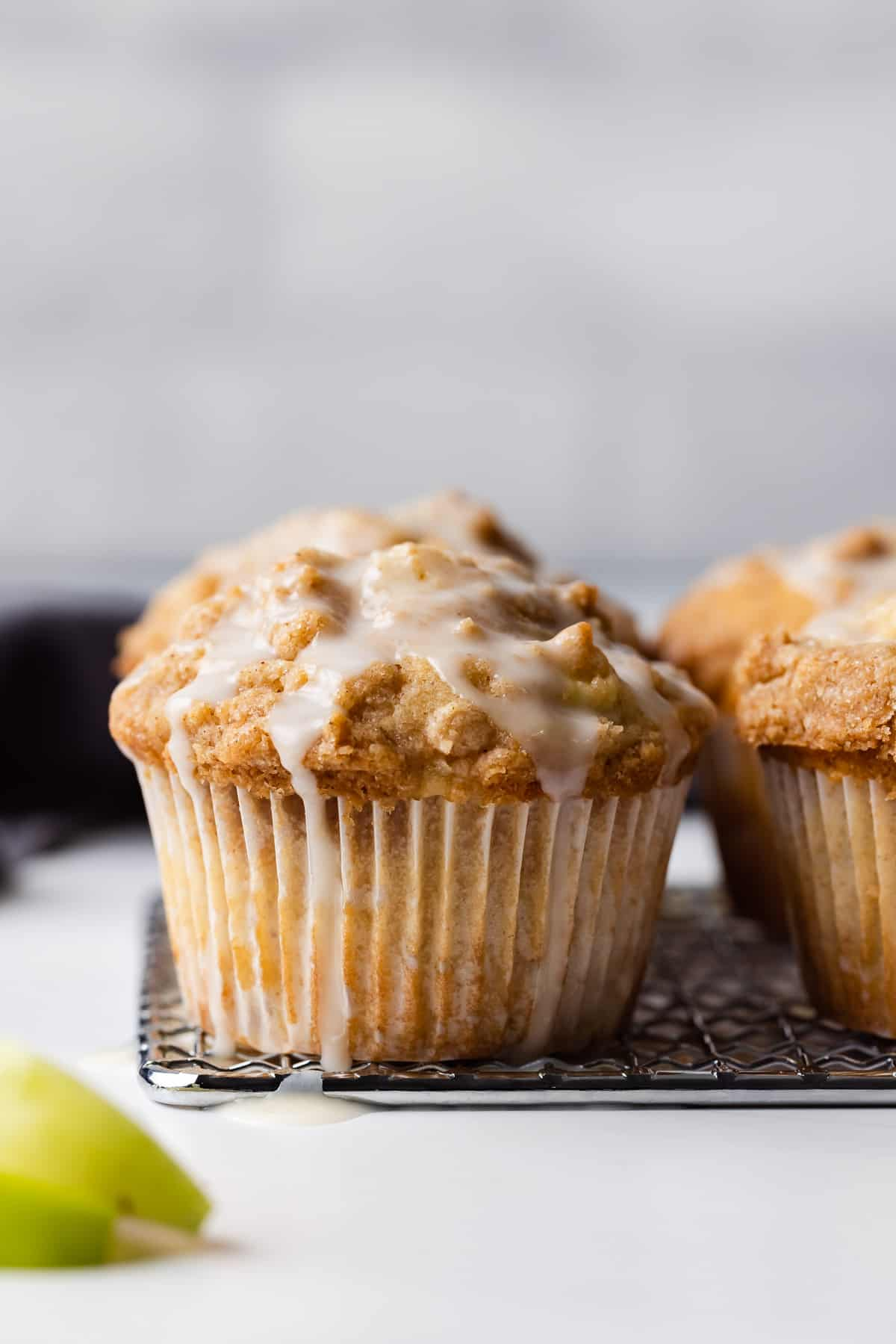 Two apple streusel muffins topped with glaze