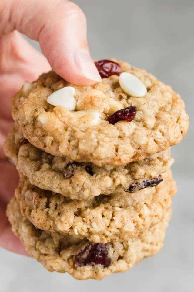 A hand holding a stack of four Cranberry White Chocolate Oatmeal Cookies.