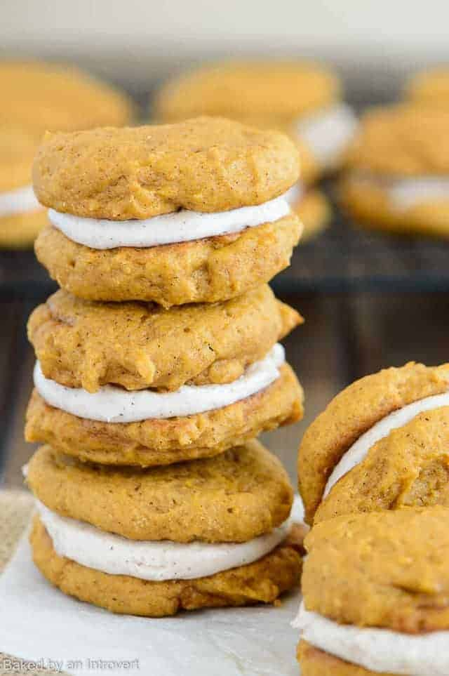 pumpkin whoopie pies stacked on parchment paper