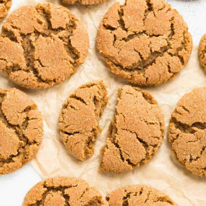 A close up view of chewy gingersnap cookies broken in half on a pieces of brown parchment paper.