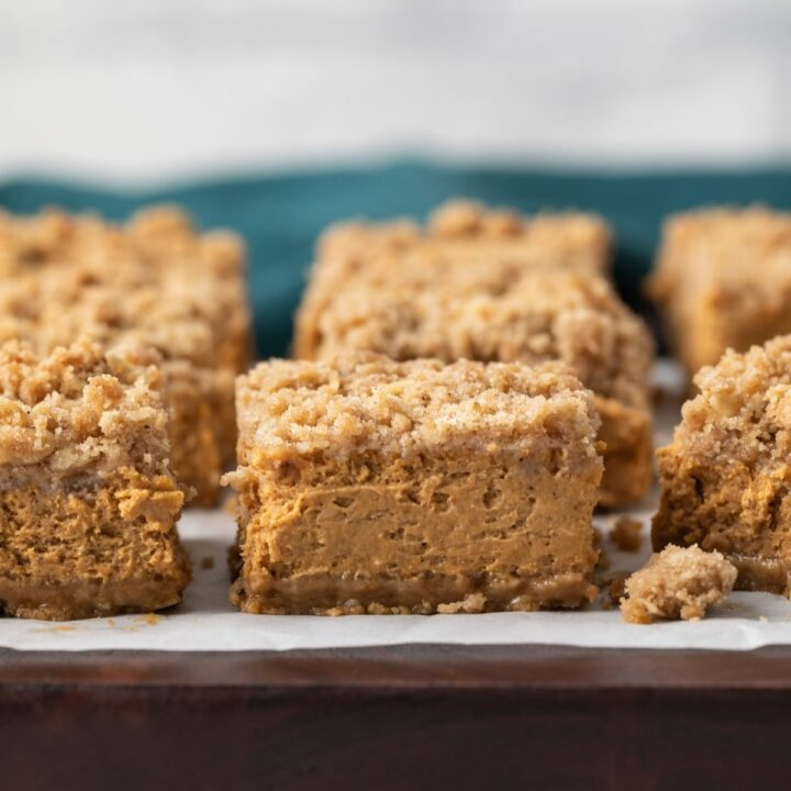 pumpkin bars on brown board with parchment paper