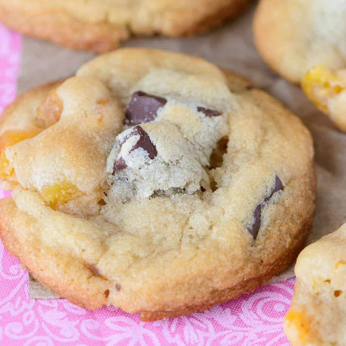 angled view of chocolate chunk apricot cookies on a pink fabric