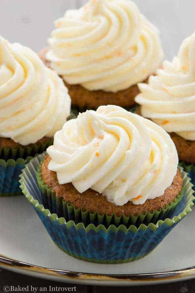 side view of Gingerbread Cupcakes with Orange Mascarpone Frosting on a white plate