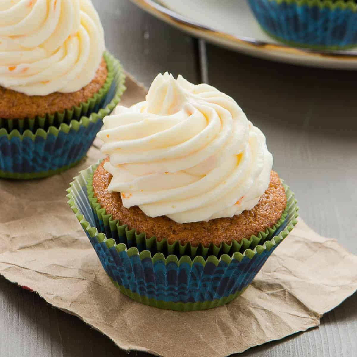 angled view of Gingerbread Cupcakes with Orange Mascarpone Frosting on brown paper