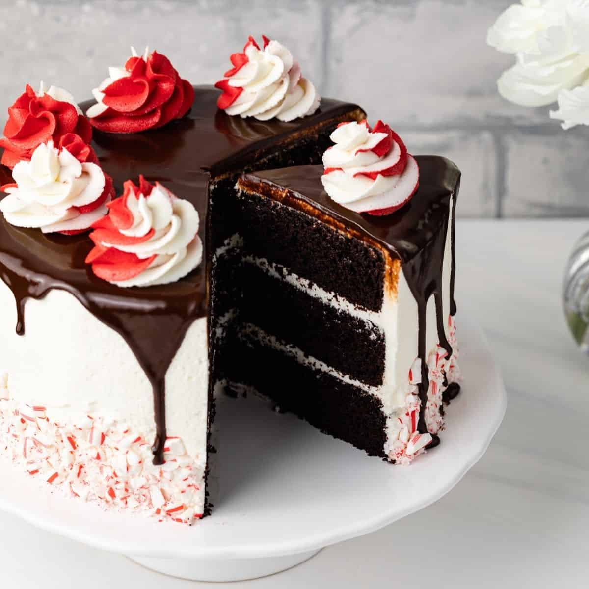 Chocolate cake with white icing decorated with a fudge drip and crushed candy canes sitting on a white cake stand.