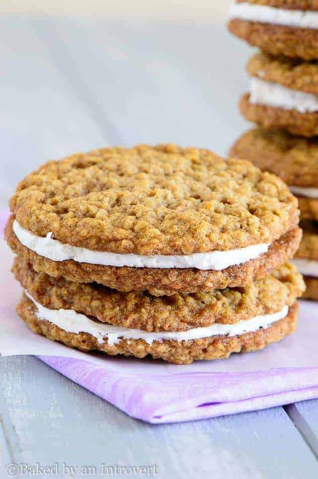 Two oatmeal cream pie cookies stacked on a purple napkin.