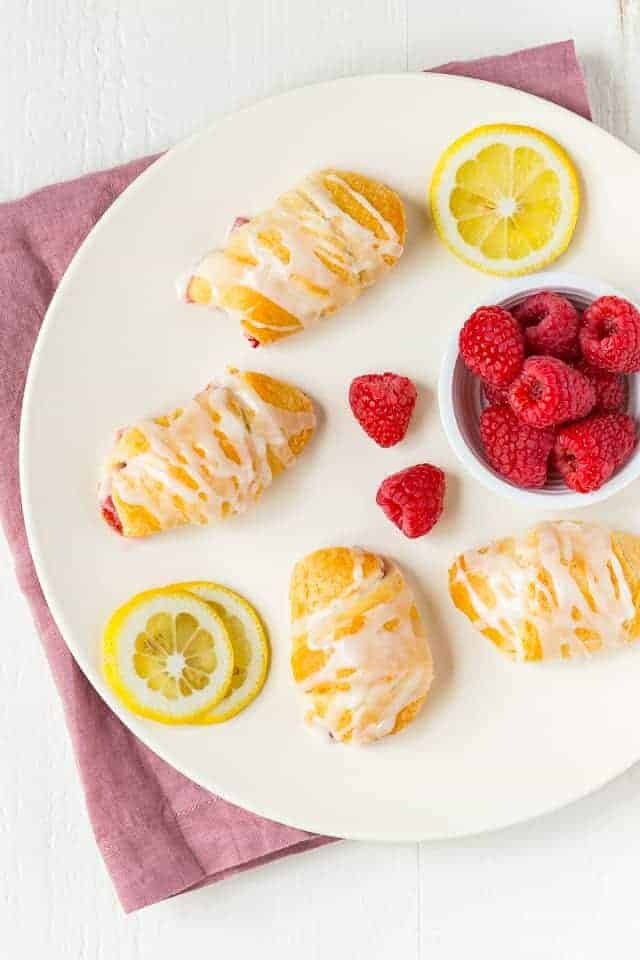 overhead view of raspberry lemon crescent rolls on a white plate