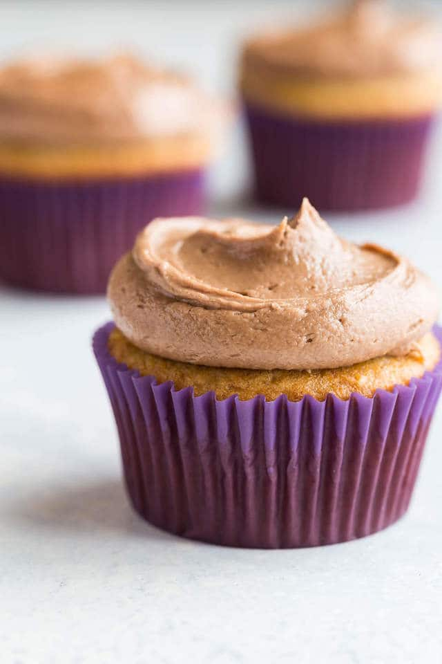 Swirls of Nutella frosting over banana cupcakes in purples cupcakes liners.