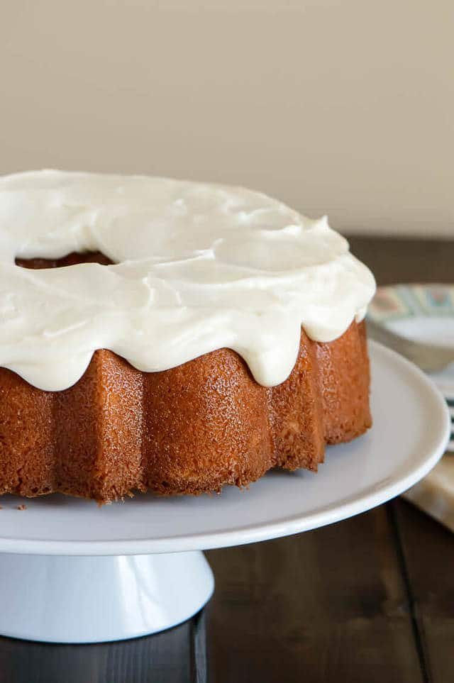 Side view glazed orange pound cake with cream cheese glaze on a white cake plate.