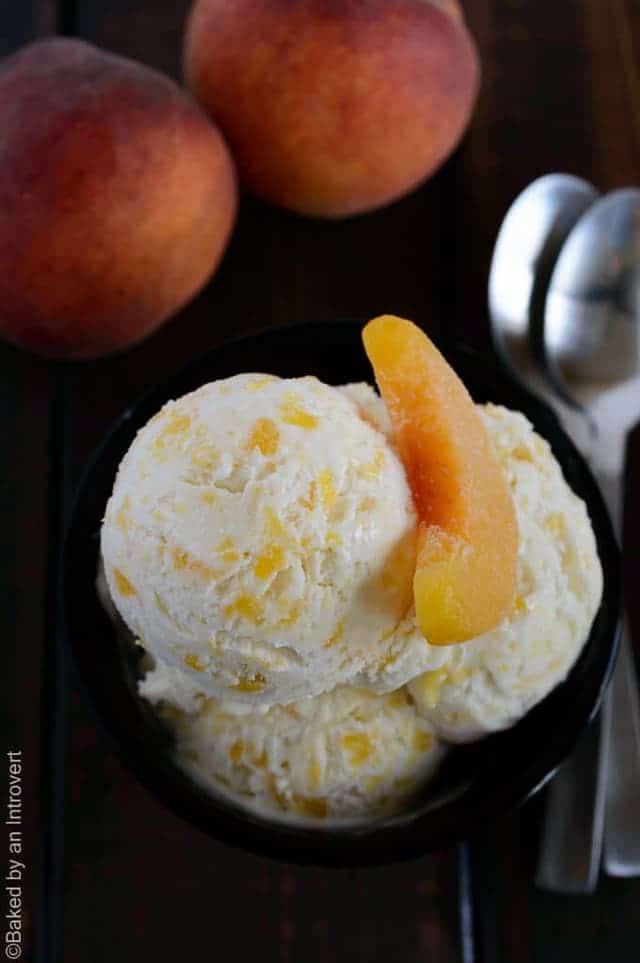Scoops of peaches and cream ice cream in a black bowl with a slice peach on top.