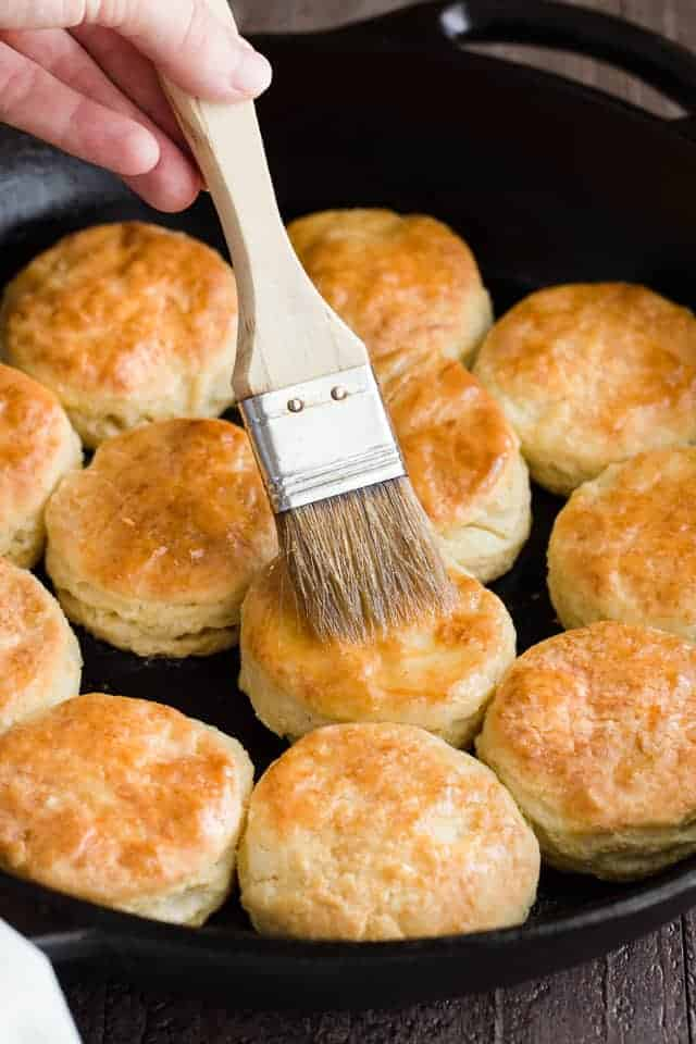 Brushing butter over over honey cream cheese biscuits with a pastry brush.