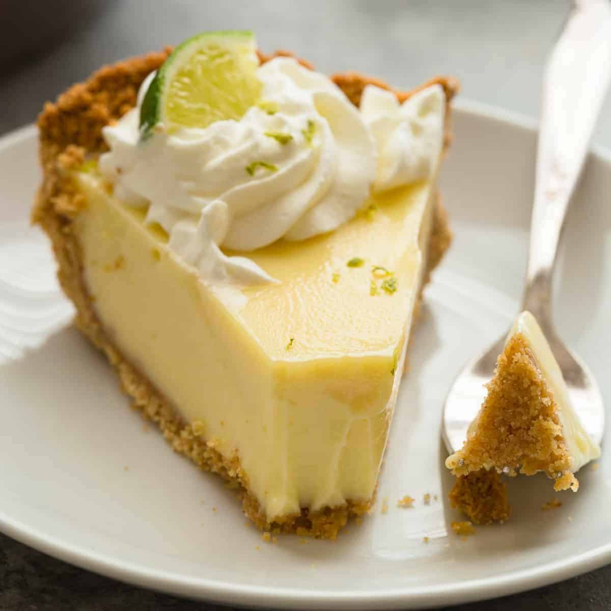 Close up view of lime pie in a white plate with a fork taking out a bite.
