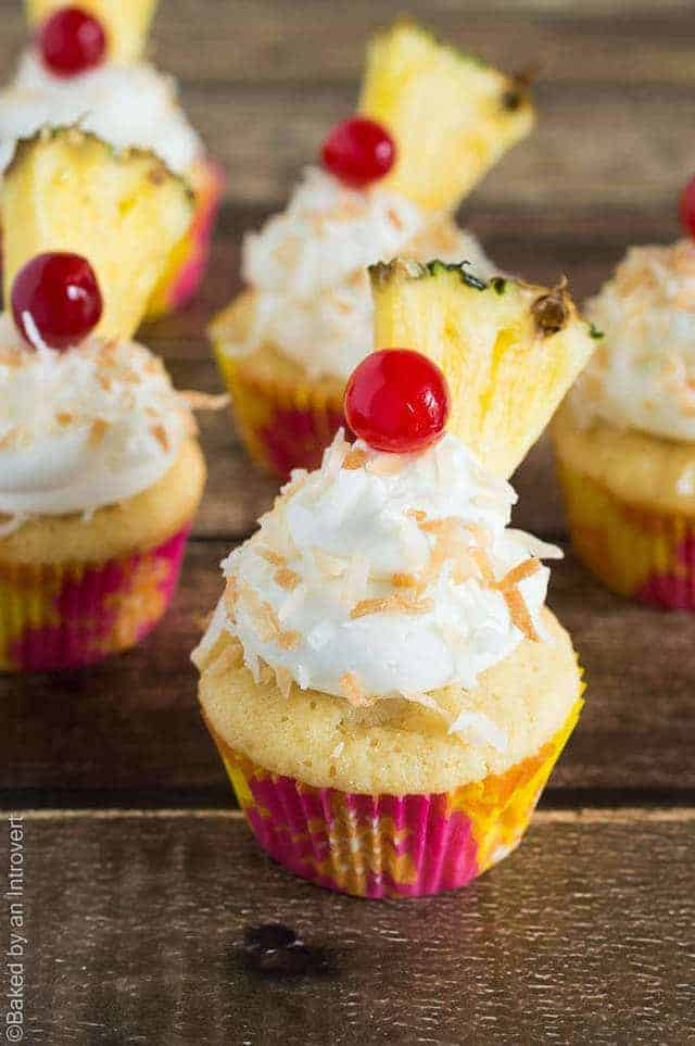 Angled view of pina colada cupcakes on wood background.