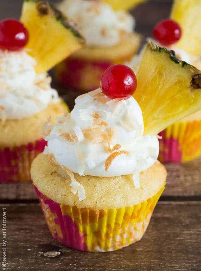 Side view of pina colada cupcakes with coconut frosting, a cherry, and pineapple slice on top.