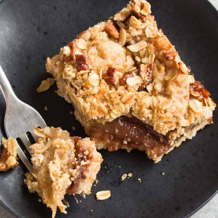 Apple Streusel Bar on a black plate with a fork taking a bit out of it.