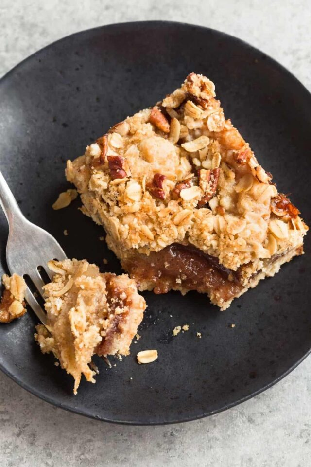 Sinfully decadent Apple Streusel Bars with a shortbread crust, gooey cinnamon apple center, and a crunchy pecan streusel on top.