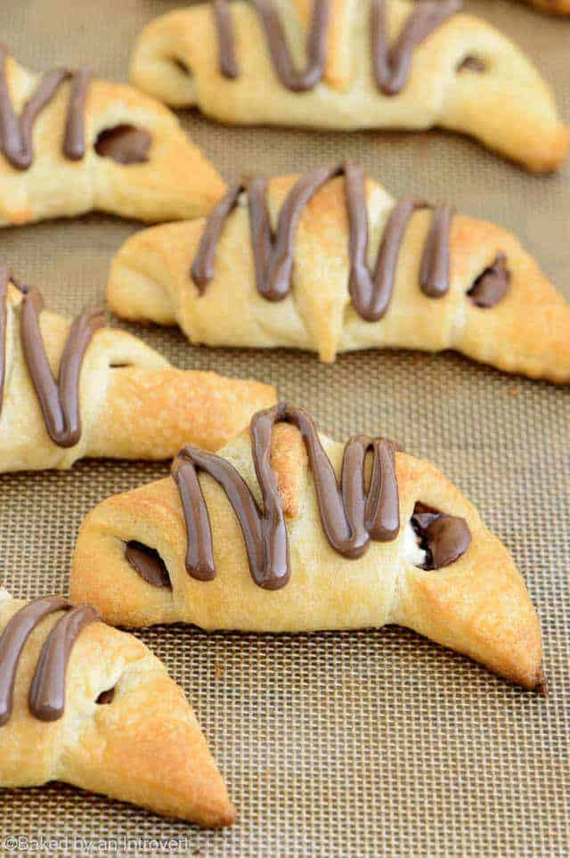 Angled view of Nutella cream cheese crescent rolls on a baking sheet lined with a silicone mat.