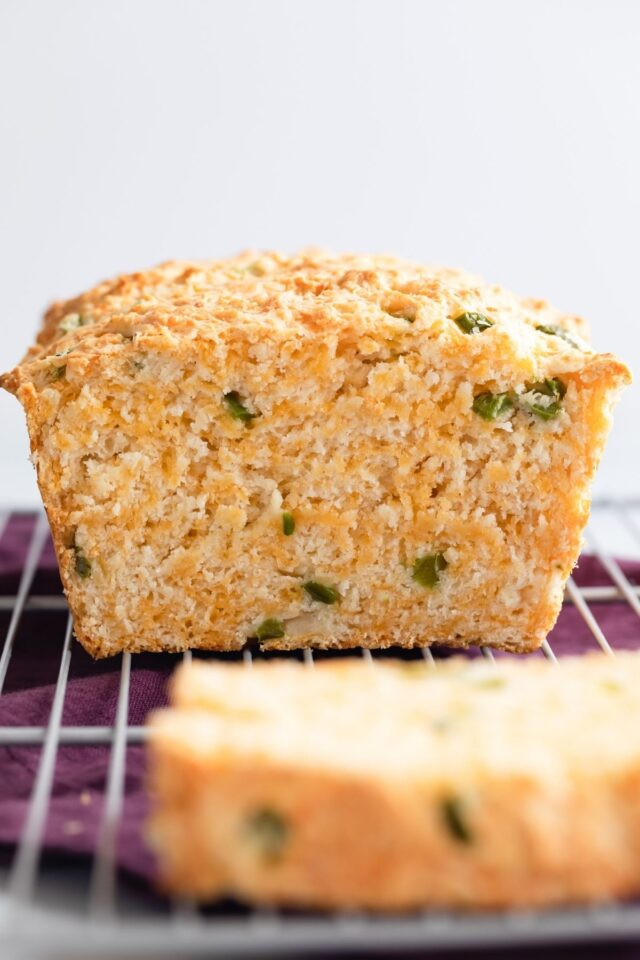 cheddar jalapeno buttermilk bread on a wire rack with a slice cut out