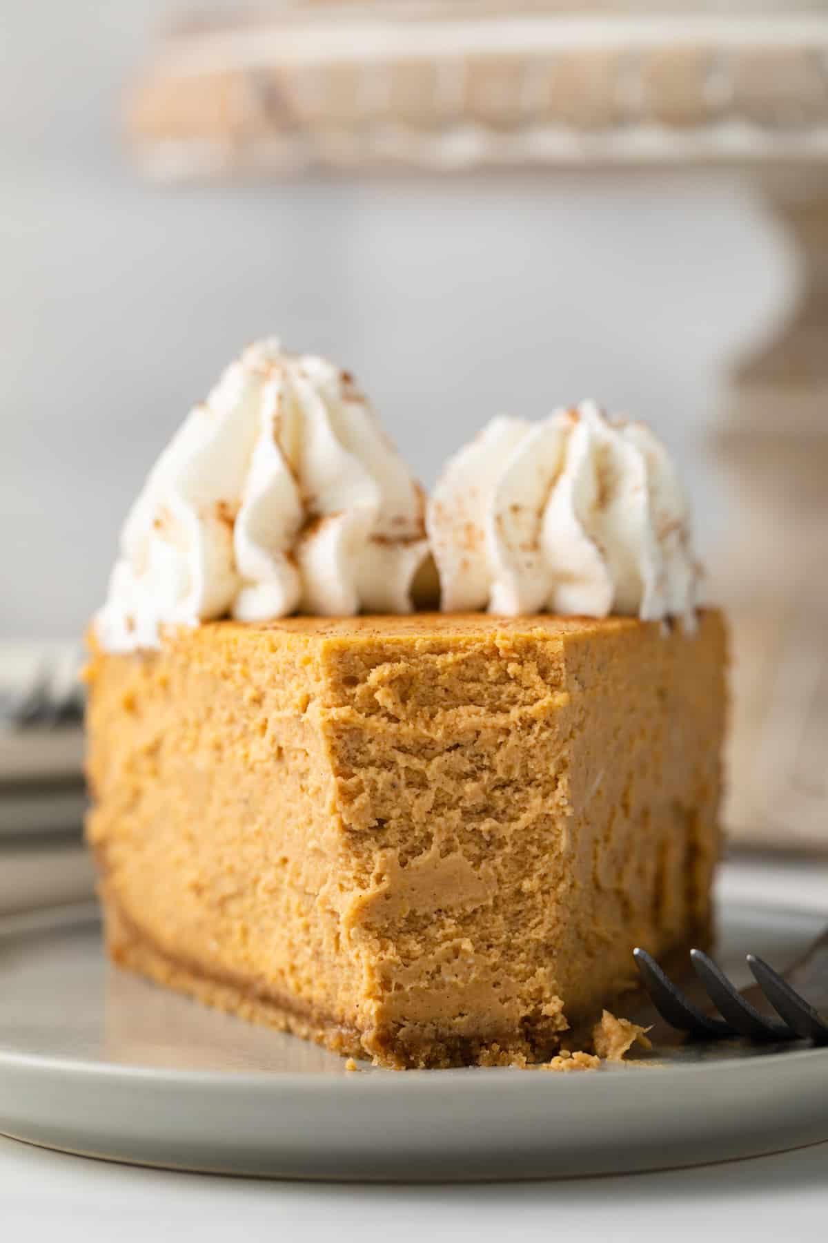 Angled view of a slice of Pumpkin Cheesecake on a white plate with a fork taking a bite out.