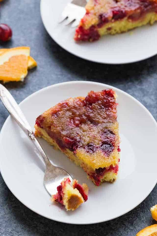 A slice of Cranberry Orange Upside Down Cake on a plate with a fork taking a bite out.