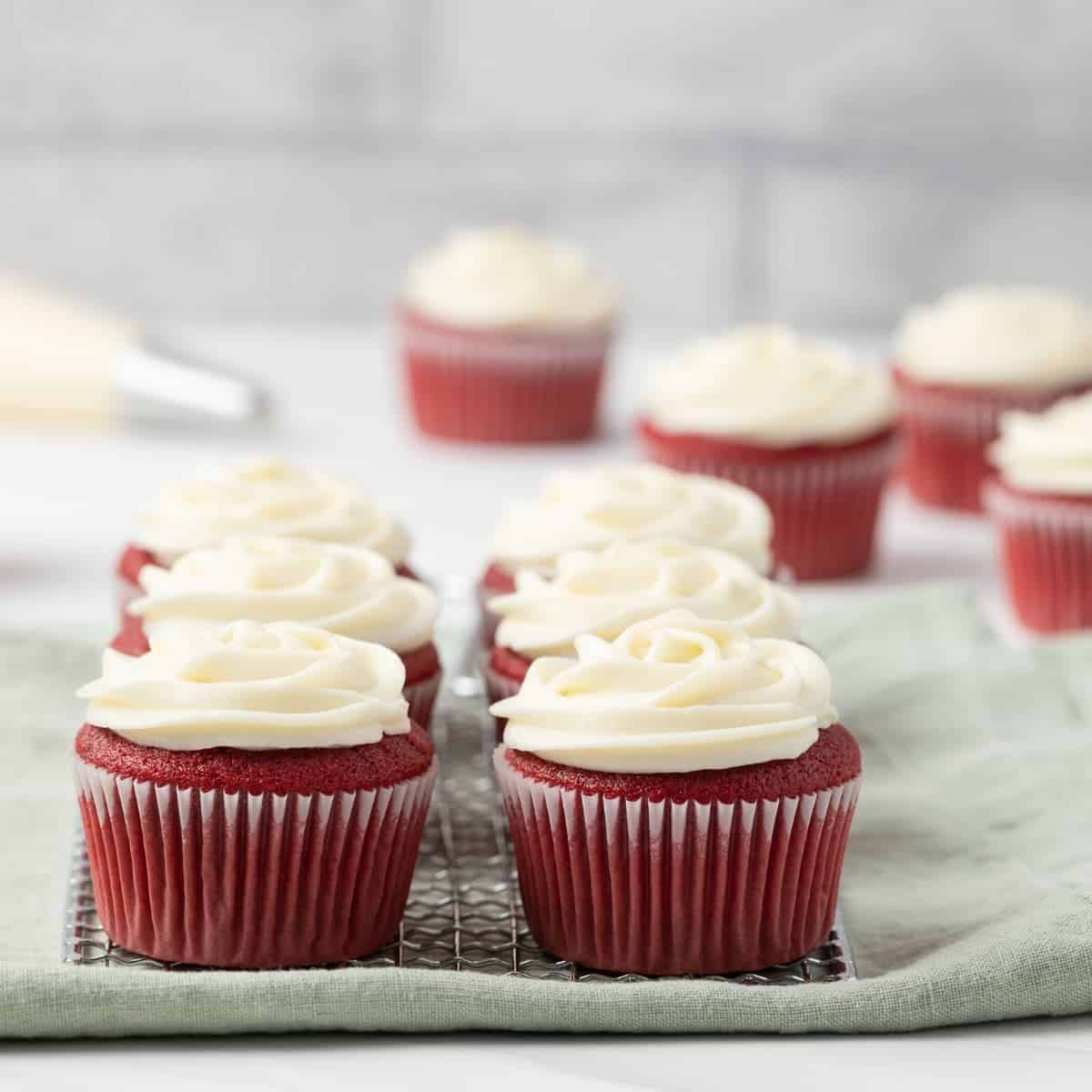 red velvet cupcakes with cream cheese on a wire rack with a green napkin underneath