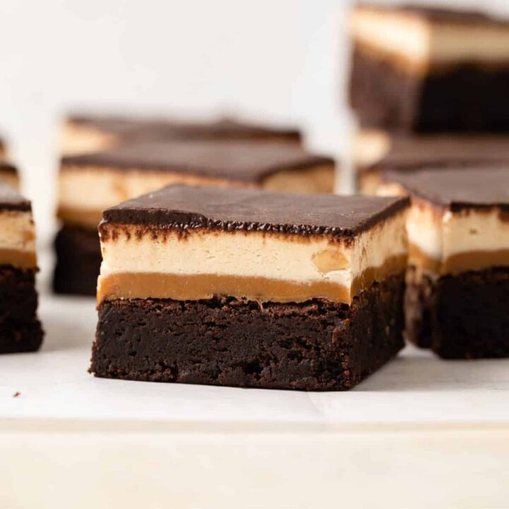 A fudgy chocolate brownie with layers of gooey caramel, chewy nougat, and chocolate ganache over the top sitting on white parchment paper with a fork taking a bite out.