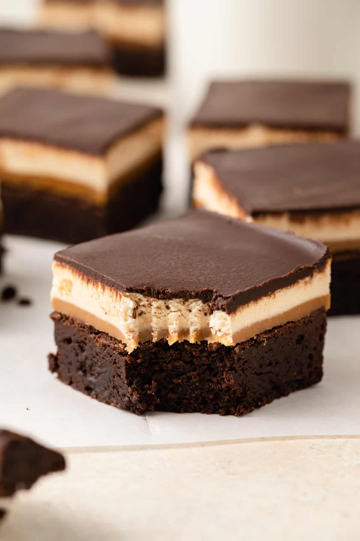 Above view a fudgy chocolate brownie with layers of gooey caramel, chewy nougat, and chocolate ganache over the top.