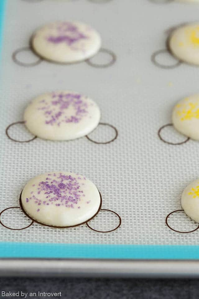 Unbaked macaron shells on a baking sheet.