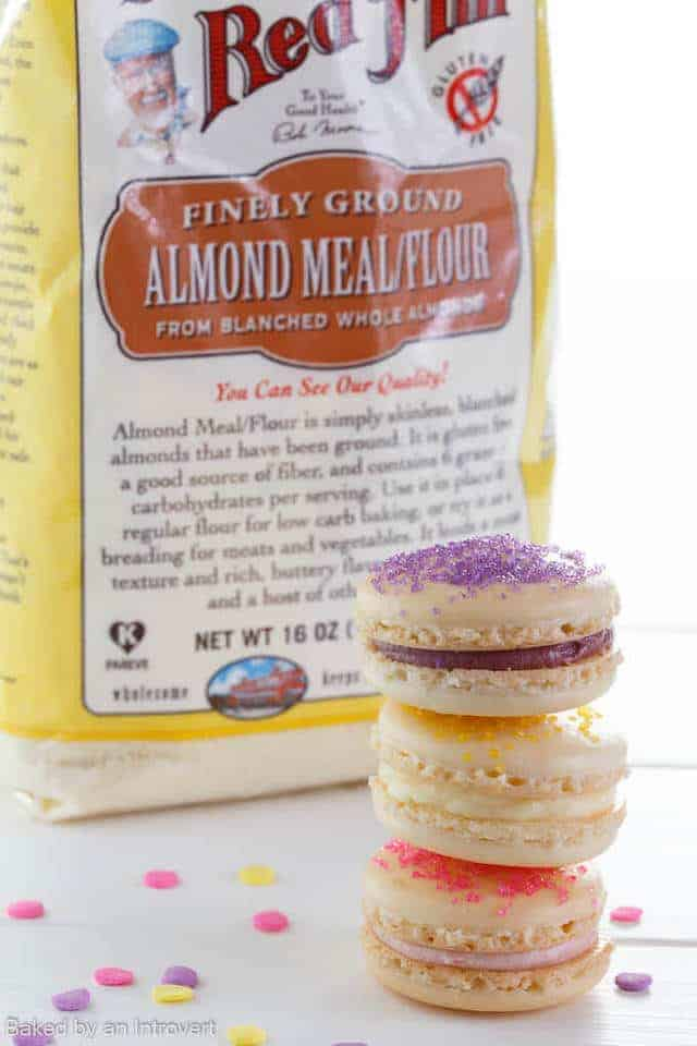 Three macarons stacked in front of a bag of almond meal.
