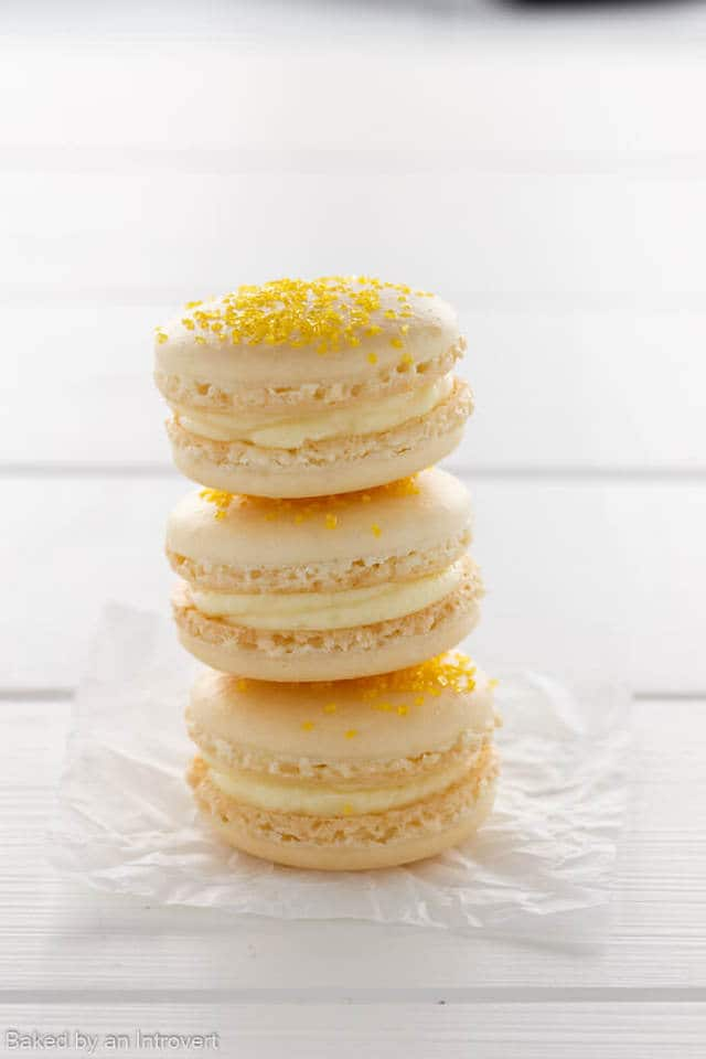Three cheesecake macarons stacked on a white background.