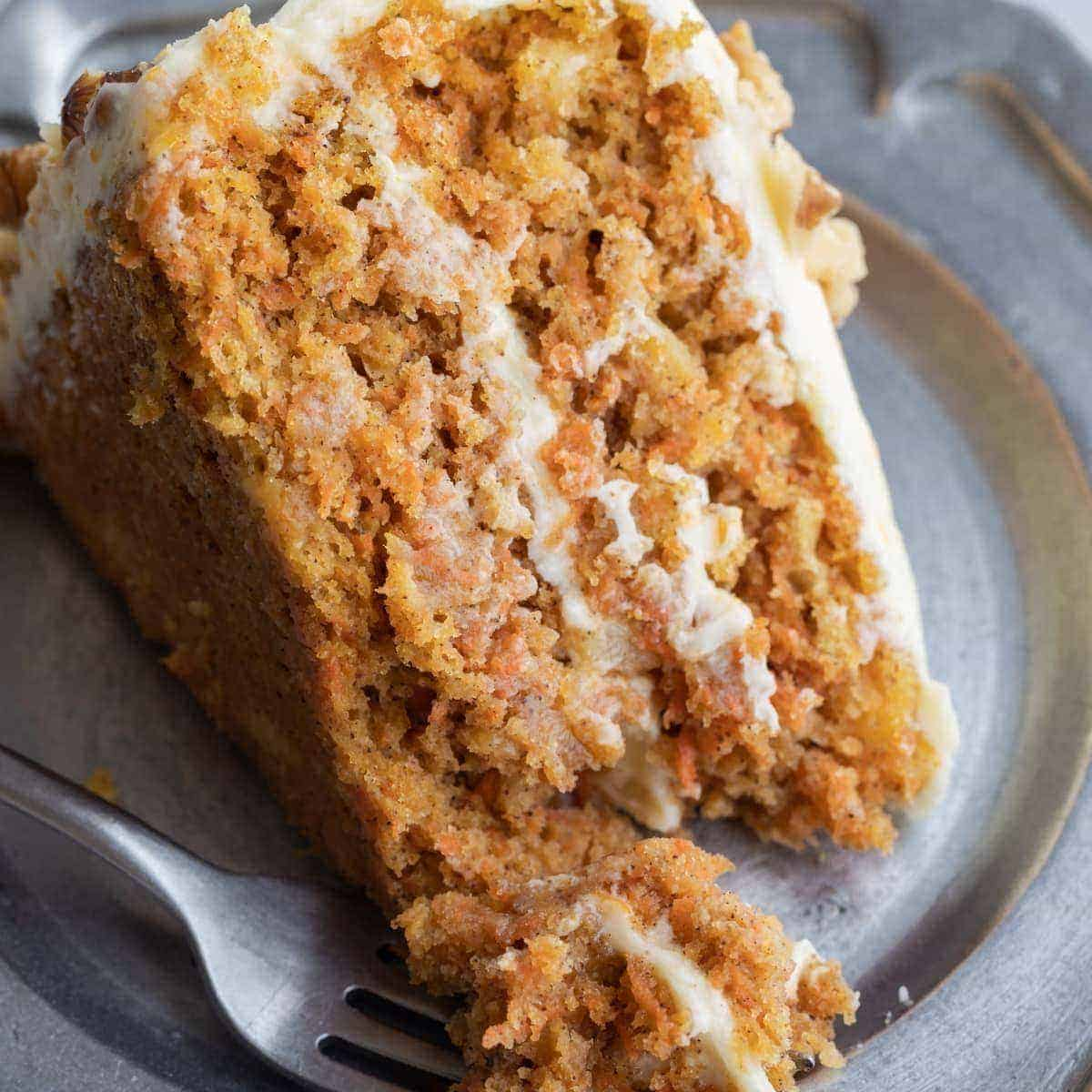 carrot cake with pineapple on a pewter plate with fork
