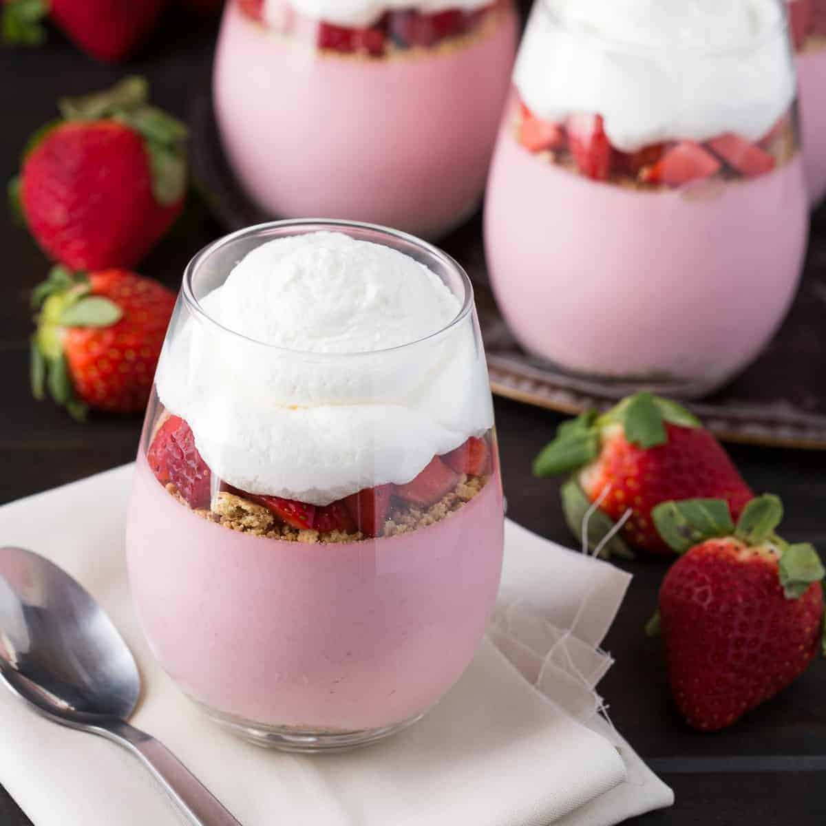 Strawberry cheesecake mousse in glass cups topped with whipped cream.