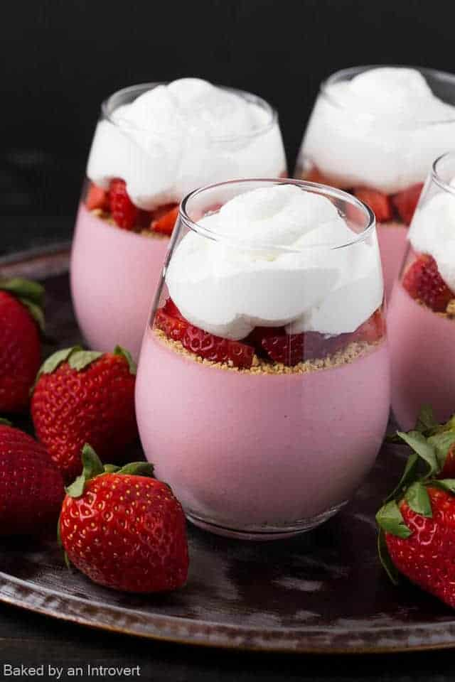 Strawberry cheesecake mousse in glass jars with strawberries scattered around.